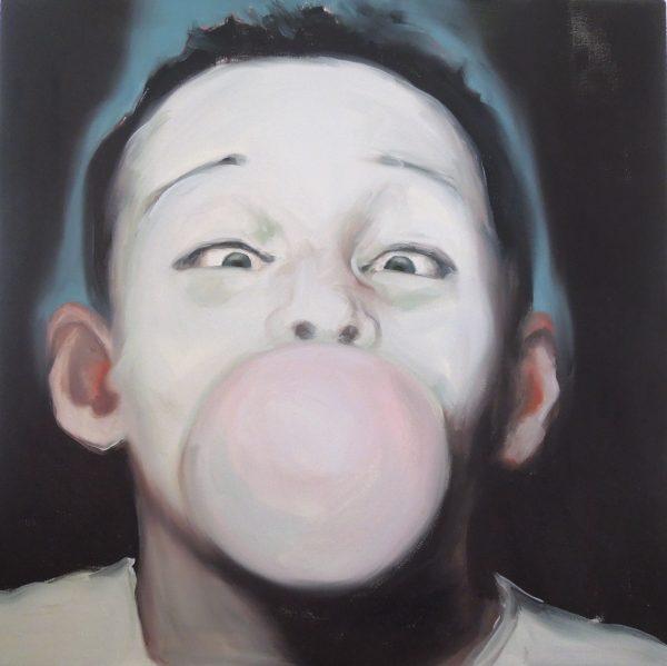 Portrait of a boy blowing bubble-gum bubble