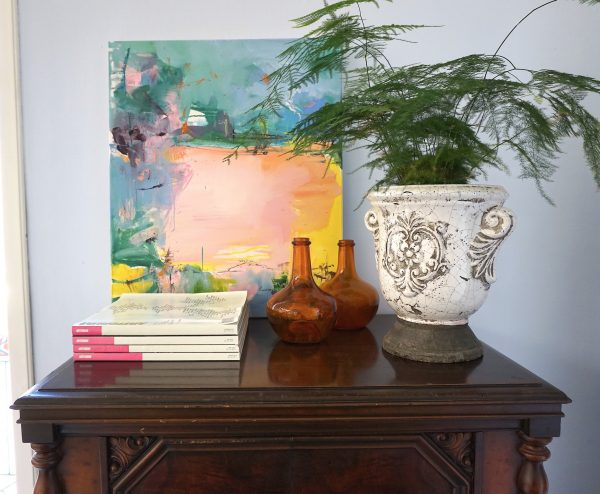 Abstract expressionist landscape oil painting Mood 33 against wall framed by earthenware pot, plant & bottles