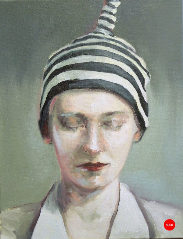 Head and shoulders portrait of woman with eyes closed and wearing a striped hat.