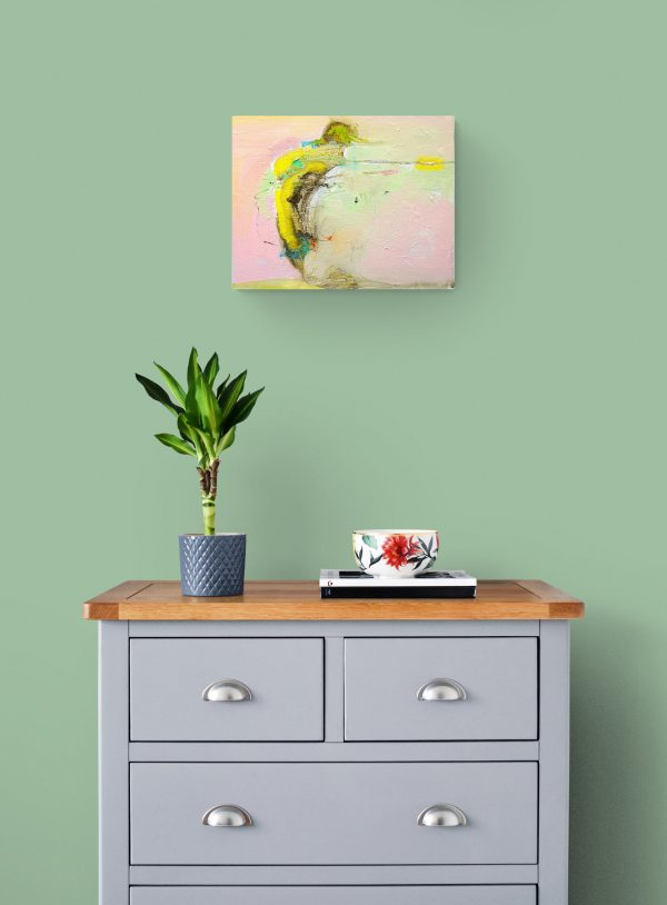 Abstract expressionist painting in pink, yellow and other colours hanging on wall above cabinet